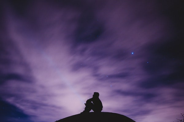 silhouette of a man at night looking up at the sky