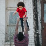 Dad-playing-and-throwing-his-kid-in-the-air-and-the-kid-smiling-and-laughing