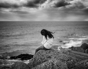 woman sitting on a rock overlooking the ocean looking down and sad