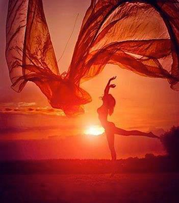 woman throwing a blanket in the air with the sunset behind her