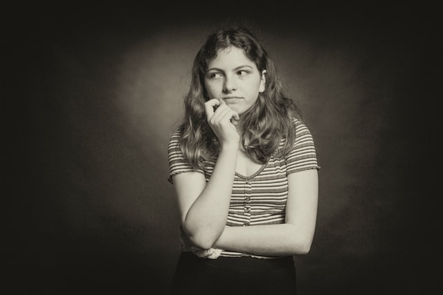 woman in striped shirt contemplating