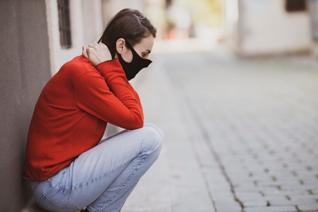 person wearing mask sitting on curb