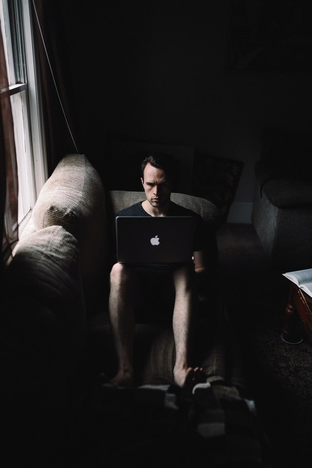 person-sitting-on-couch-looking-at-laptop