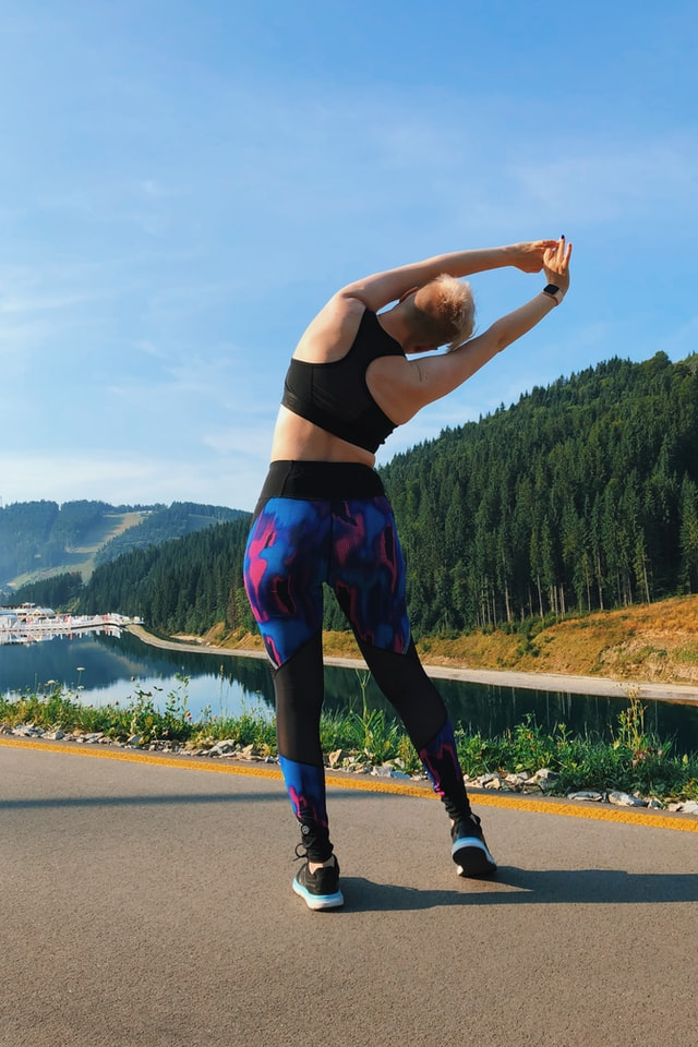 woman in workout clothing stretching on a road in front of trees and a river